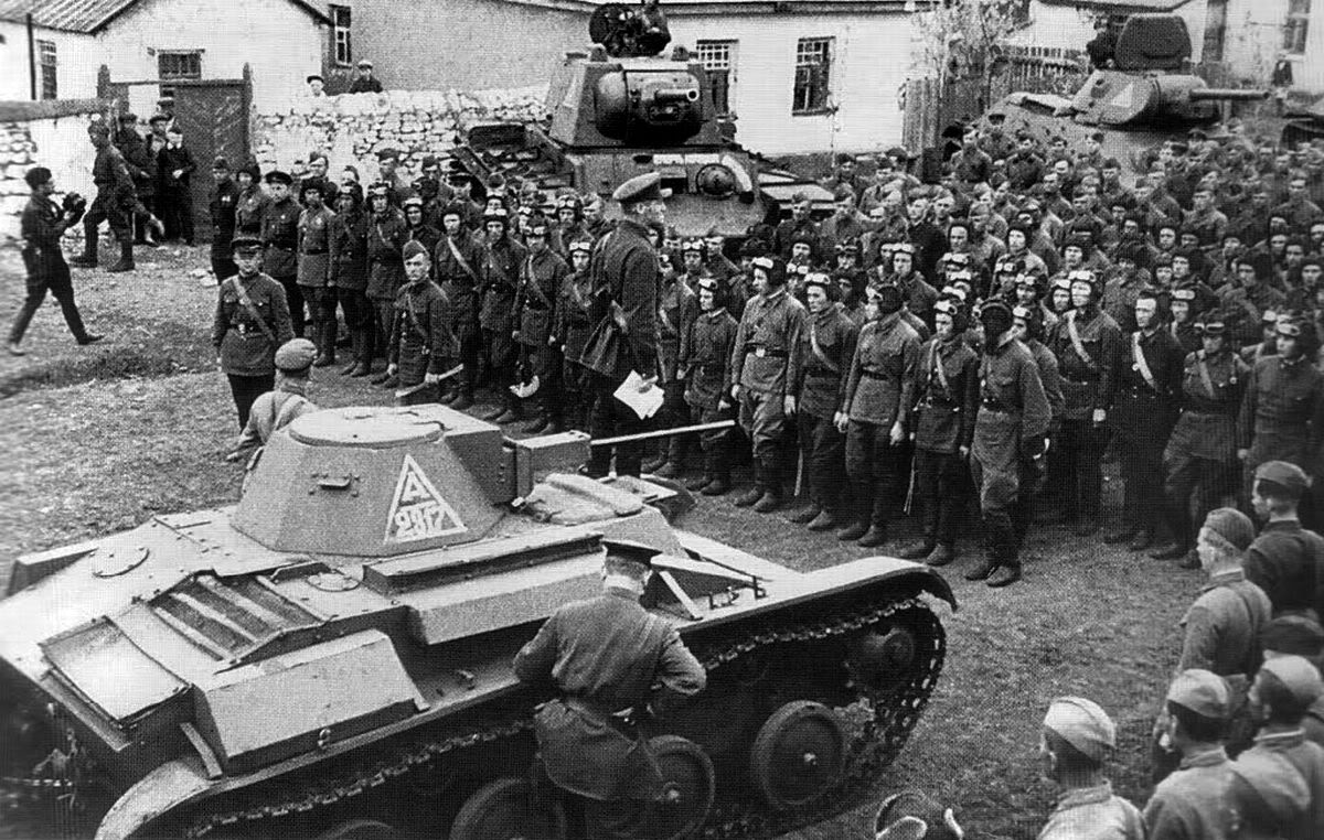A Commissar stands next to a T-60 whilst giving a speech to Soviet tank crews in May, 1942.