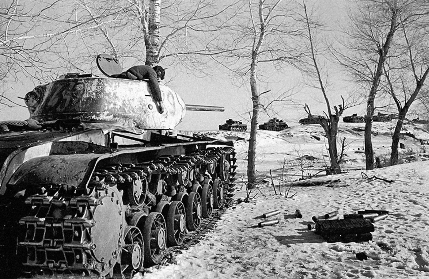 A knocked out KV-1S circa 1943, with the dead commander hanging from his cupola. It had just engaged the German column in the background.