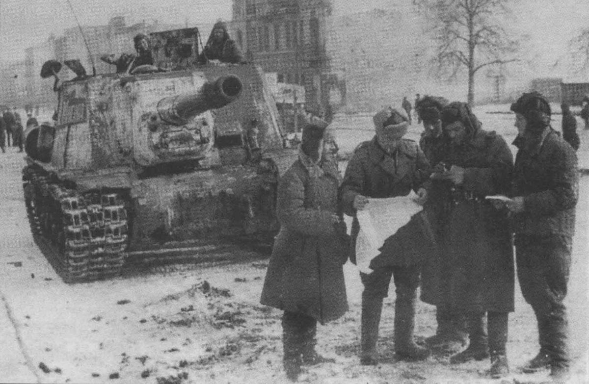 The commander of an ISU-152 and other officers consult a map during WWII.