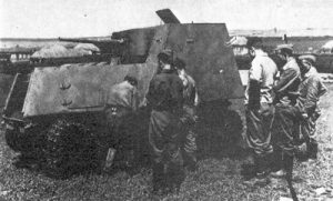 A KhTZ-16 has its track repaired. The vehicle also appears to be camouflaged