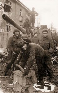 The crew of an ISU-152 appear to be cleaning their boots with Nazi banners