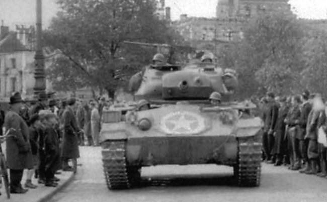 M24 Chaffee of D company, 27th Tank Battalion, 20th Armored Division driving down the streets of Munich on 30th April 1945.