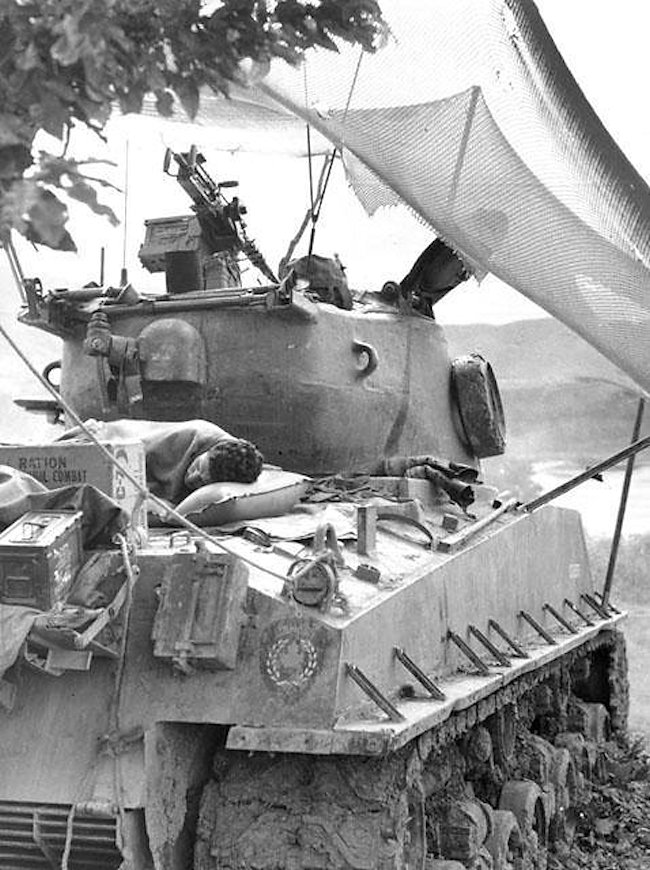 Exhausted tank crews sleep when ever they can. Notice the rear deck cover stop to the right of the soldier's head