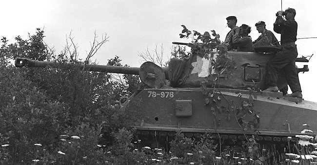Canadian M4A2(76)W HVSS Sherman tank crews using available cover to ambush the 'enemy' on a training exercise.