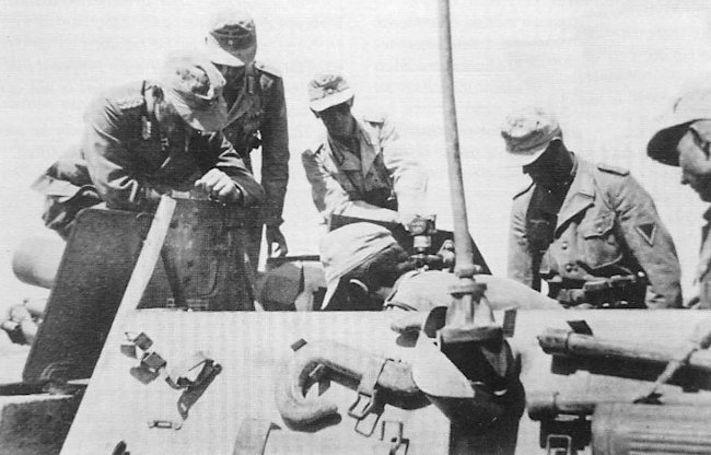 The flap in the gun shield was opened to use the shorter periscope gun sight for direct fire targets. The taller gun sight was used for indirect fire targets