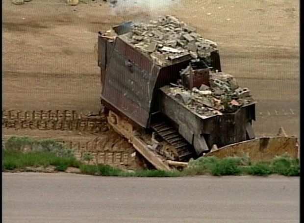 The armored bulldozer preparing to rip through a building