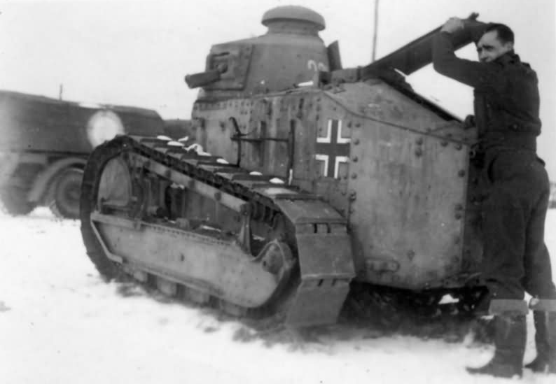 German soldier looking under the hood of a PanzerKampfwagen 18R 730(f).