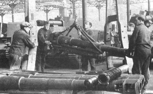 10.5cm gun barrel being lifted by chain and rope hoist