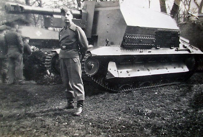 A member of the 10.5cm leFH 16 auf Geschützwagen FCM 36(f) gun crew posing for a photograph near his SPG.
