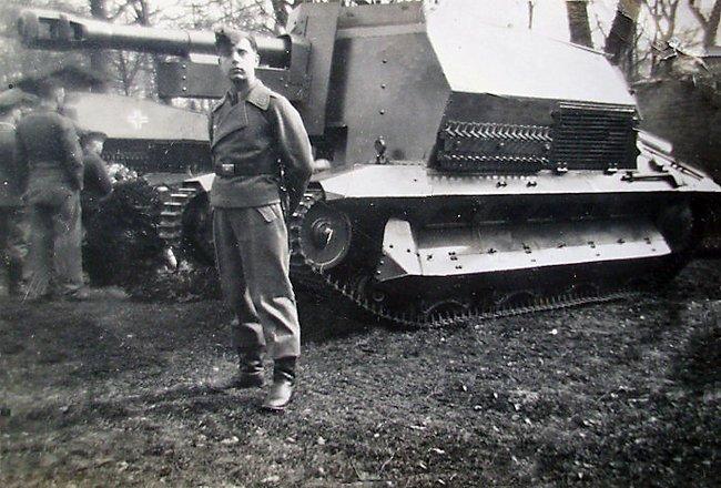 A member of the 10.5cm leFH 16 auf Geschützwagen FCM 36(f) gun crew posing for a photograph near his SPG.