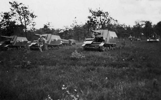 A battery of three 10.5cm LeFH 16 auf Geschutzwagen Mk.VI(e) SPGs deployed for a fire mission. Notice the tracked ammunition carrier with a trailer in the background.