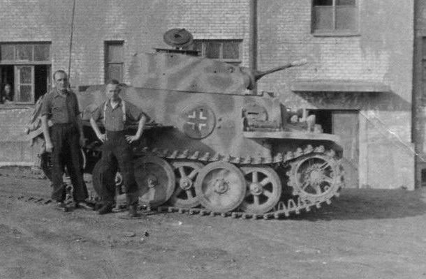 2 crew members stand beside their vehicle. The cammo pattern can also be seen.