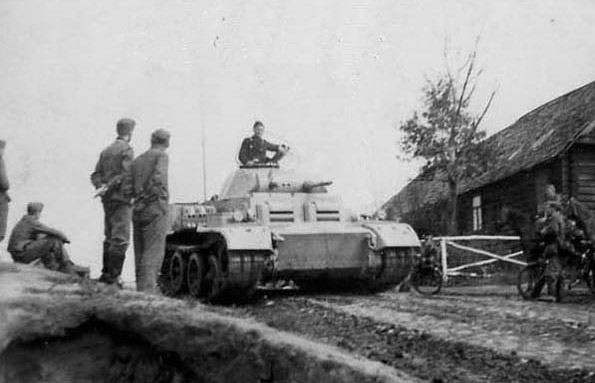 A Panzer II Ausf.J passing a group of soldiers. Notice the commander standing out of the cupola.