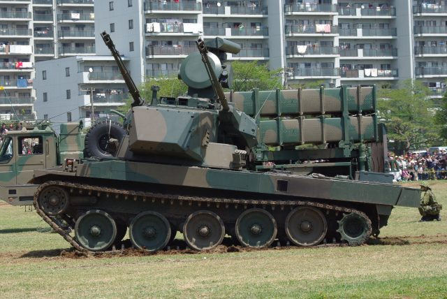A Type 87 at The Goshisu Garrison displaying it's pneumatic suspension. The vehicle in the background is a Type 03 Medium-Range Surface-to-Air missile system